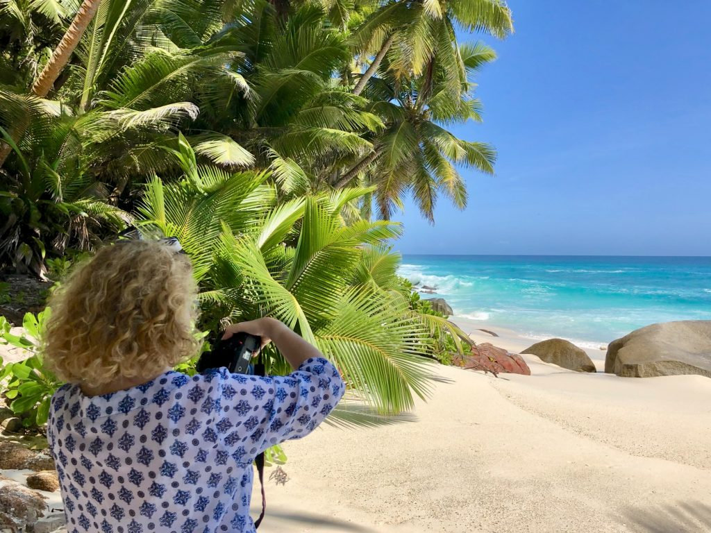 A blonde woman seen from her back and holding a camera at Anse Victorin beach on Fregate Island. Photo by Mihaela Limberea.