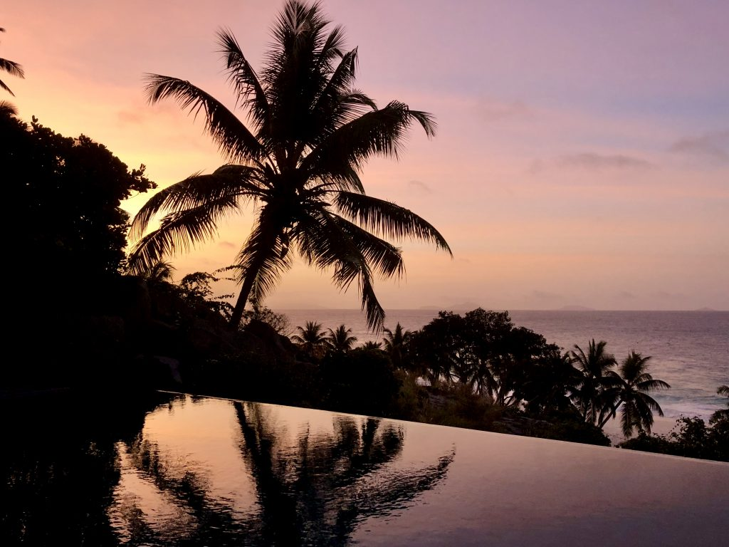 Sundown over an infinity pool and palm trees, Fregate Island. Photo by Mihaela Limberea.