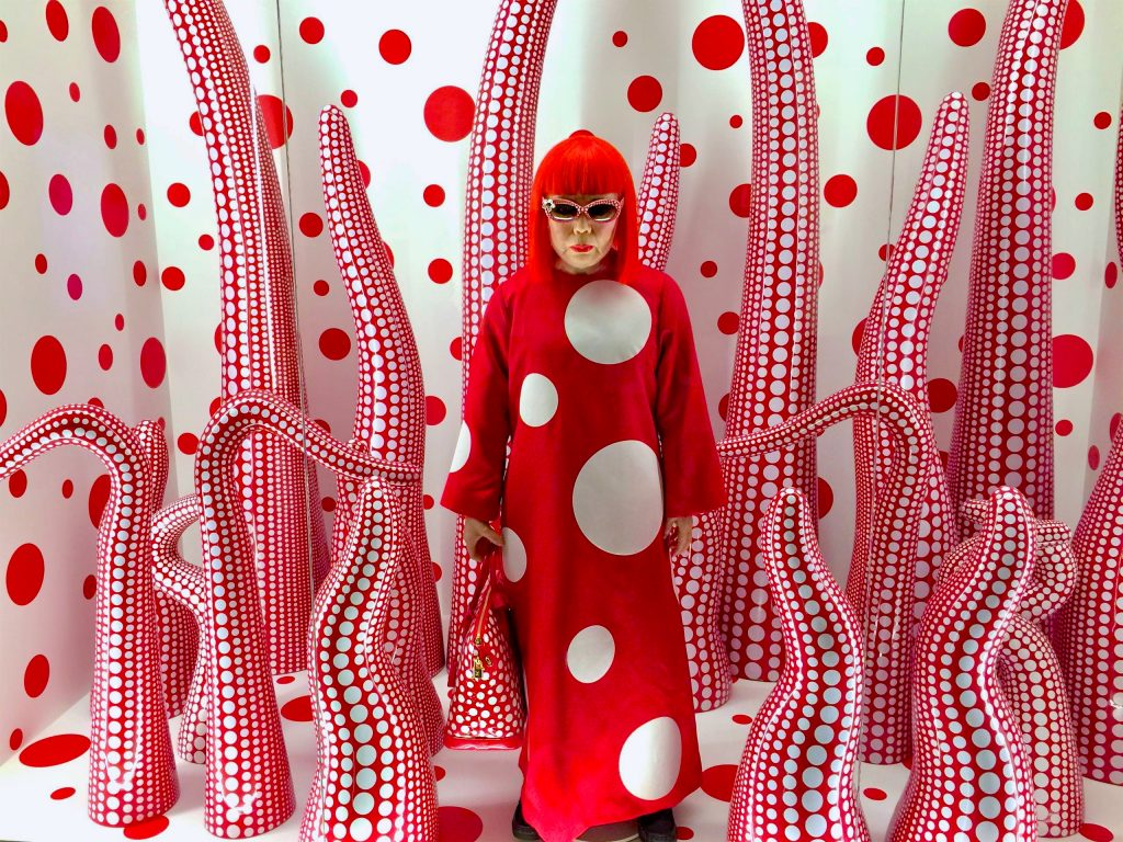 Picture of artist Yayoi Kusama as a mannequin standing in her artwork. Photo by Mihaela Limberea