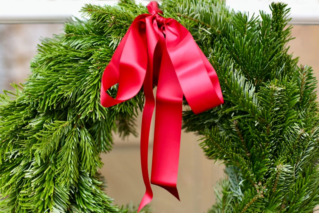 Close up of a Christmas wreath with red ribbon. Photo by Mihaela Limberea