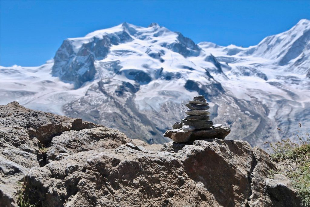 Close up of a cairn with Gornergrat glacier surrounded by mountains in the background, Switzerland. Photo by Mihaela Limberea.