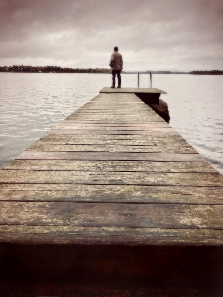 Dark mood photo of a man at the ned of a jetty. iPhone photo by Mihaela Limberea.