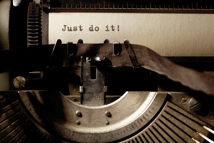 "Close up of a vintage-style typewriter with the words ""Just do it"" typed on the page."