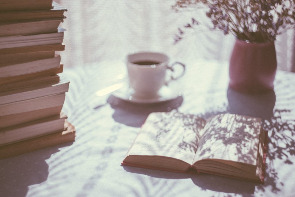 A pile of books, an open book, and a cup of coffee on a table.