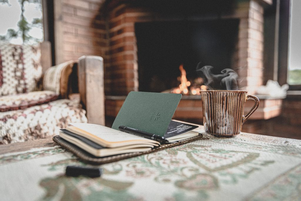 Coffee mug and notebook near a fireplace.