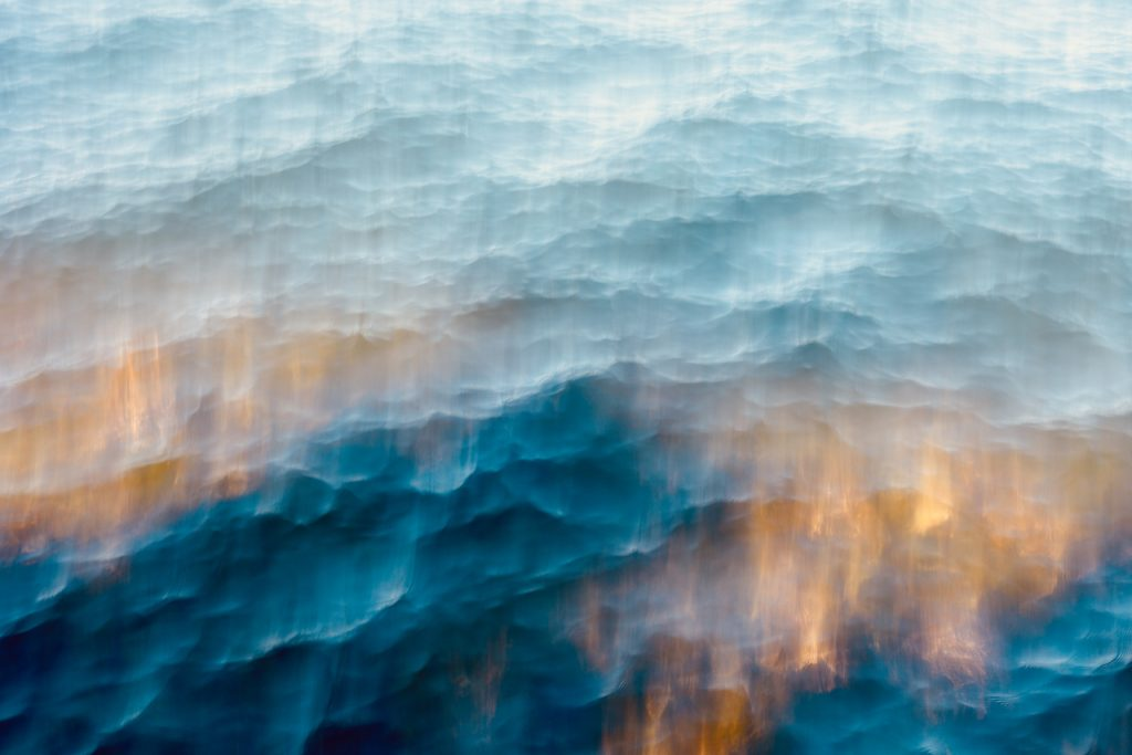 An abstract photo of ice and fire in hues of blue and orange. Photo by Mihaela Limberea