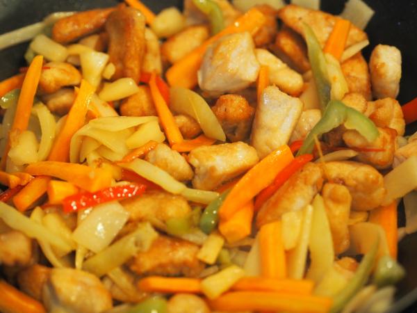 Bilde av grønnsaker og kylling blandet, klar for å helle over sausen til kylling i sursøt saus