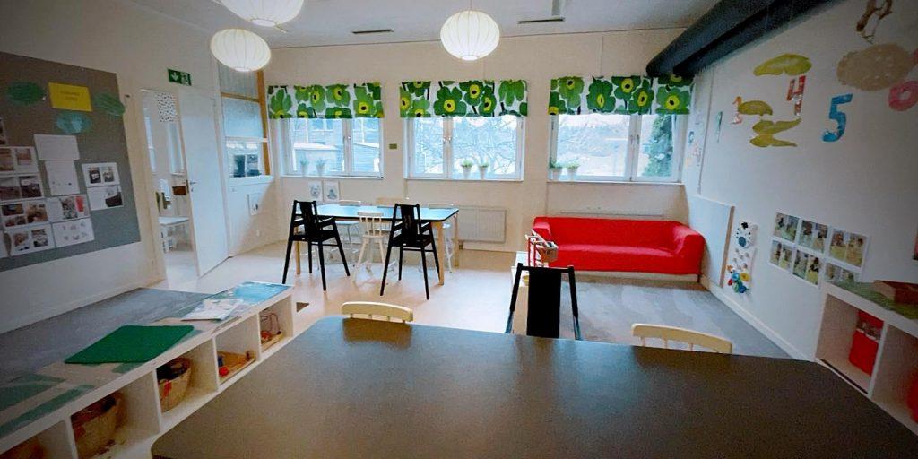 Inomhusbild på Lingonbackens förskola. Ljust och luftigt med bord, stolar och en röd soffa.