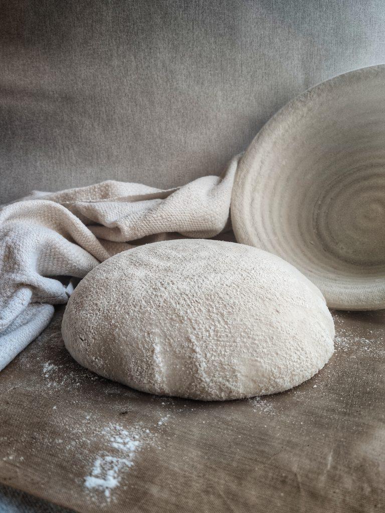 Vänder över brödet på ett bakplåtspapper. Surdegsbröd
