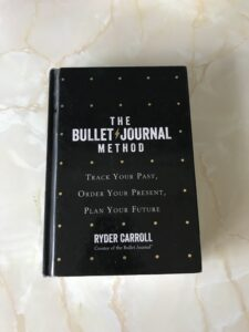 A picture of the book The Bullet Journal Method displayed on a marble background