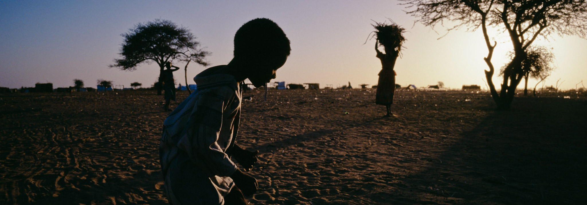 Silhouette of a child crosses in front of the camera with a silhouette of a woman carrying a bundle on her head in the background (Darfur, Sudan)