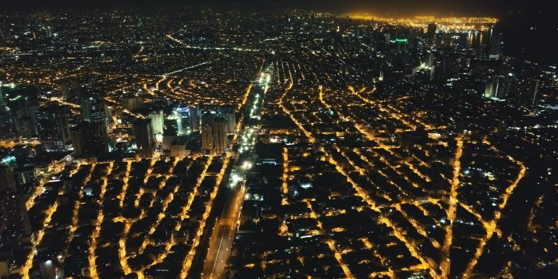 Aerial cityscape at night. Illuminated streets of Manila downtown at traffic route. Urban transport