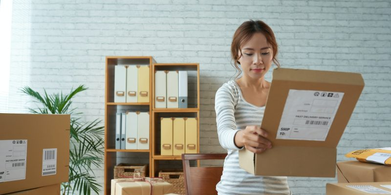 Ethnic woman opening box in post office