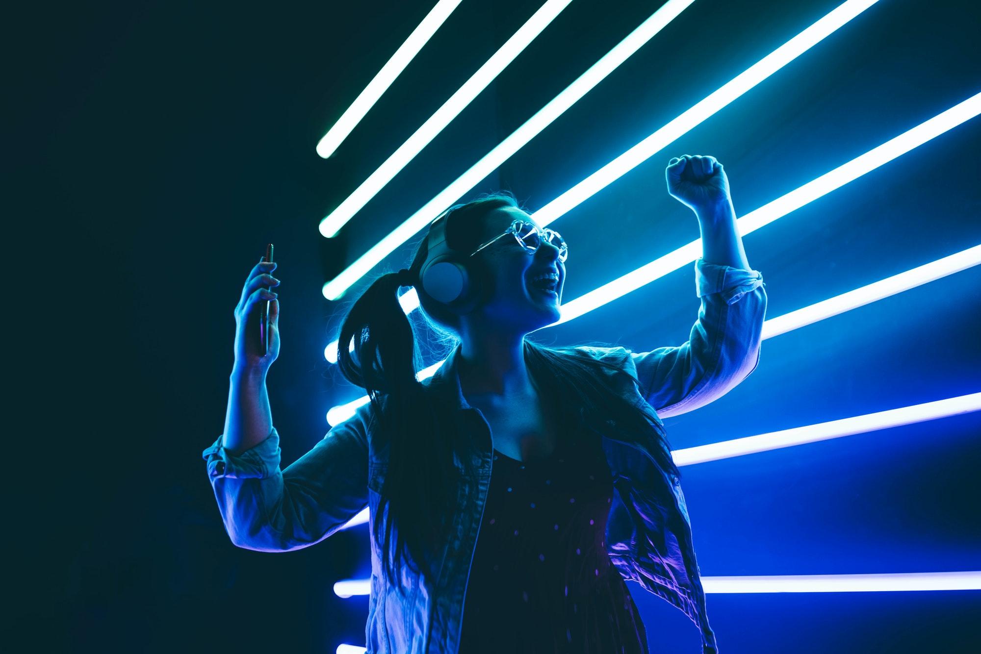 Woman in headphones listening music and dancing in neon light.