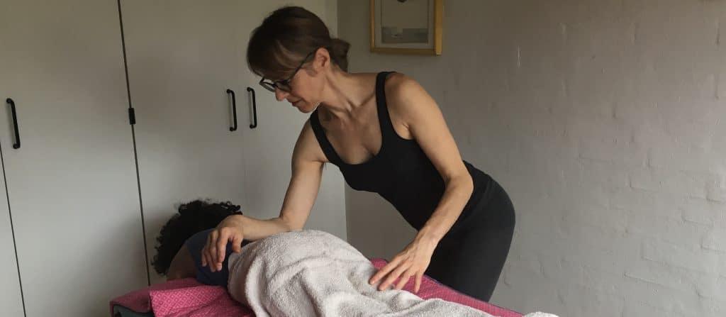 Massør Margit Andersen giver en person rygmassage på briks
