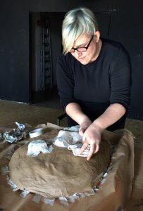 Zoe Gudovic works on her mask at the Macanudos Workshop