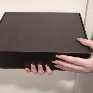 nainen pitää käsissään mustaa mysteerilaatikkoa