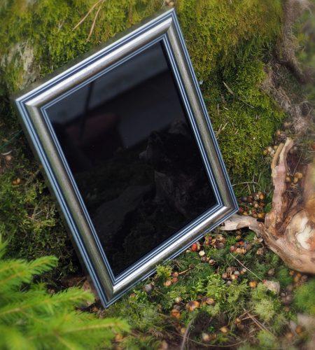 musta peili hopeisella kehyksellä, taustalla vihreää luontoa