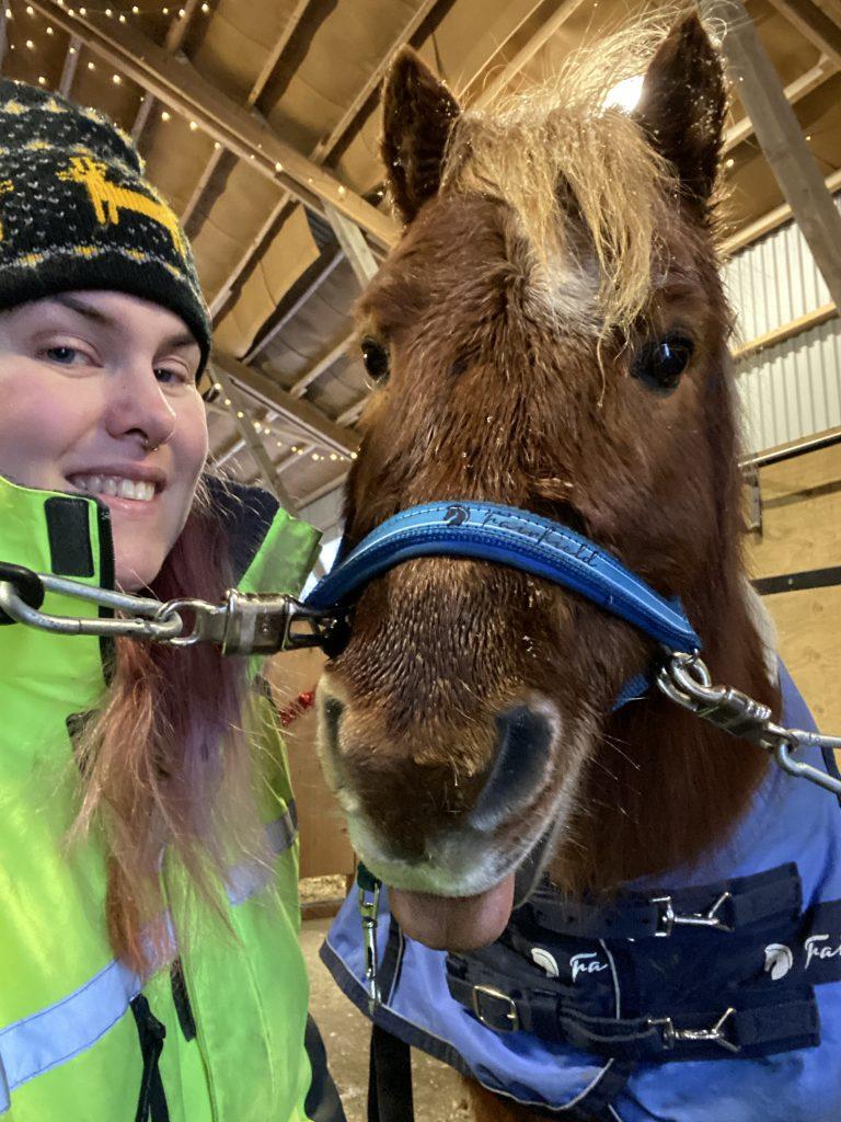 Malin Tarvainen leendes in i kameran tillsammans med ponnyn Helios.