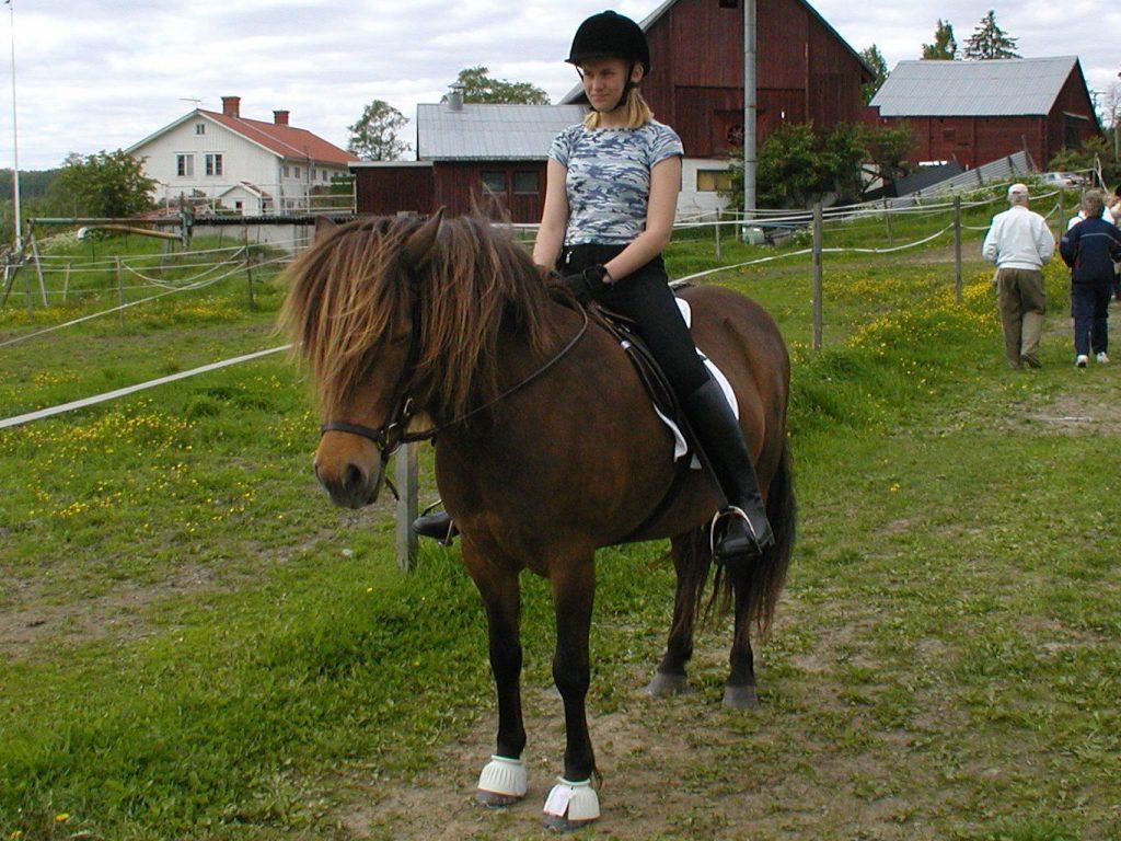 Malin Tarvainen som tonåring som sitter på sin islandshäst som heter Blá.