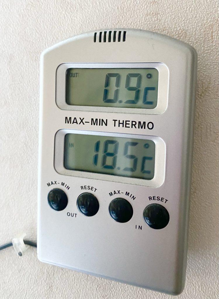 En utomhustermometer som visar 0.9 grader celsius.