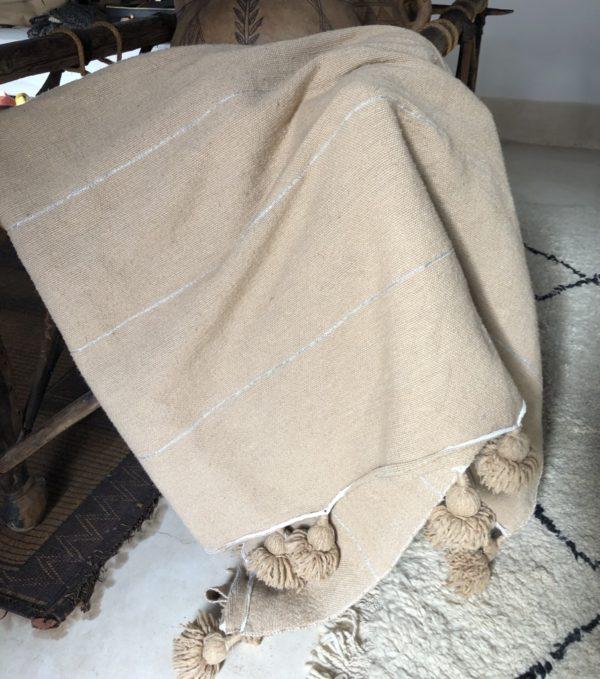 plaid med pompom fra Marokko - over stol og Beni Quarain gulvtæppe