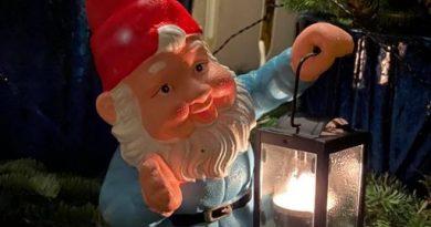 Bild på en porslinstomte som håller i en lykta med ett värmeljus i.