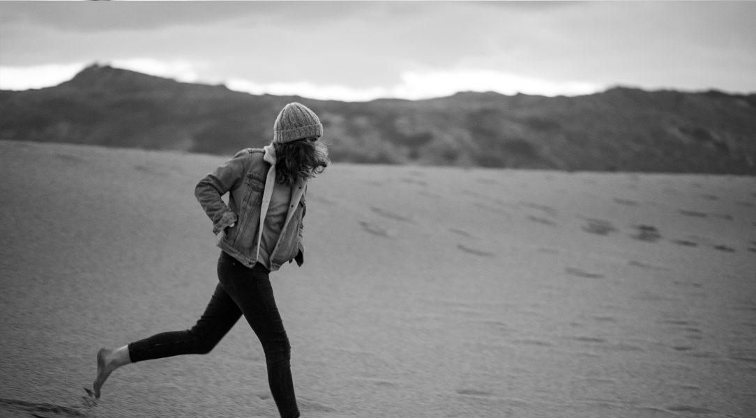 Die Sängerin Marie Rauschen rennt an einem herbstlichen Tag durch den Sand.