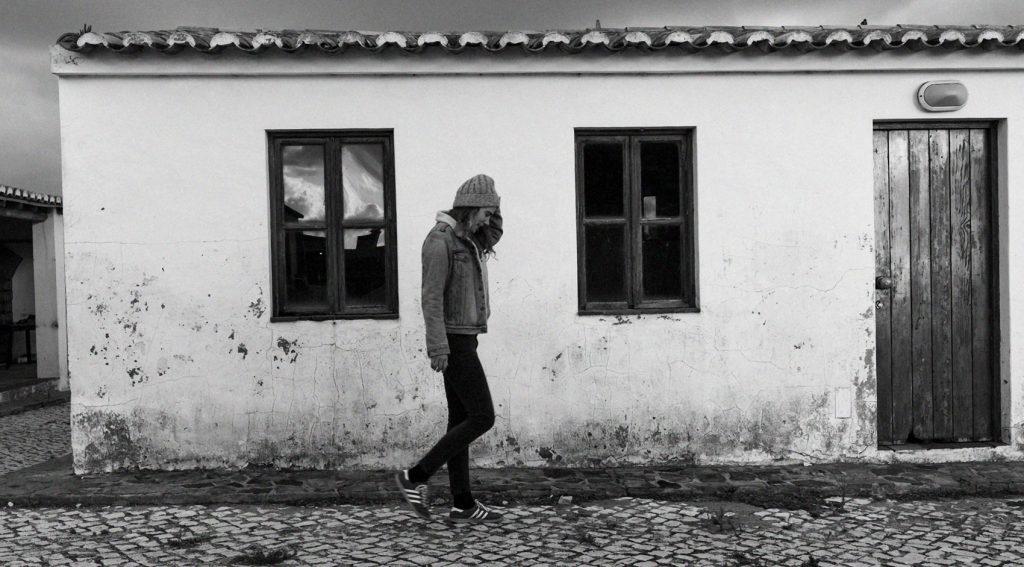 Die Singer-Songwriterin Marie Rauschenvor geht gedankenversunken einem kleinen Haus am Strand entlang.