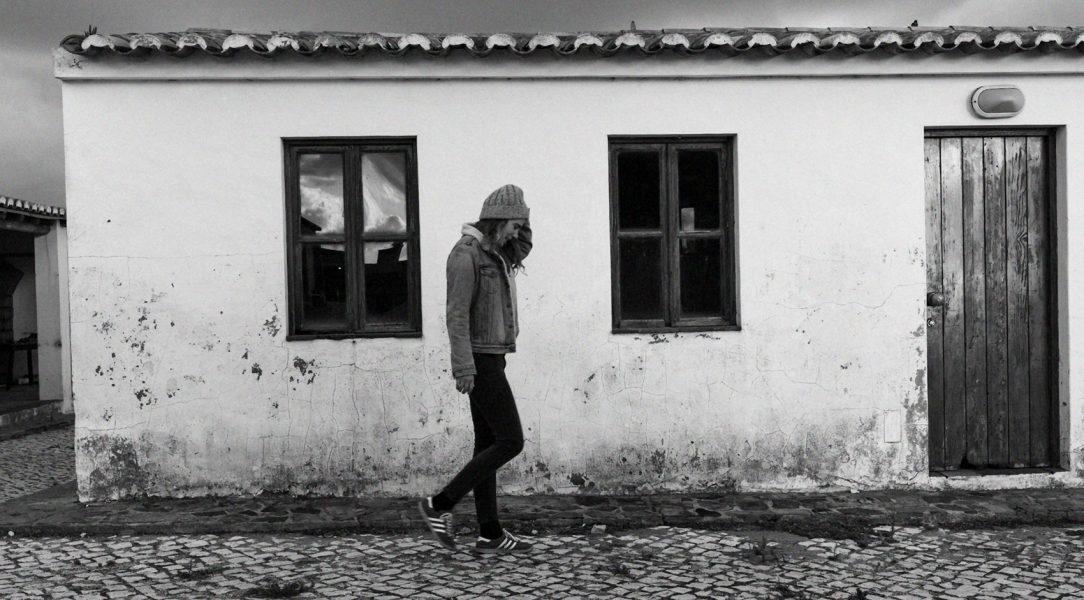 Die Singer-Songwriterin Marie Rauschen vor geht gedankenversunken einem kleinen Haus am Strand entlang.