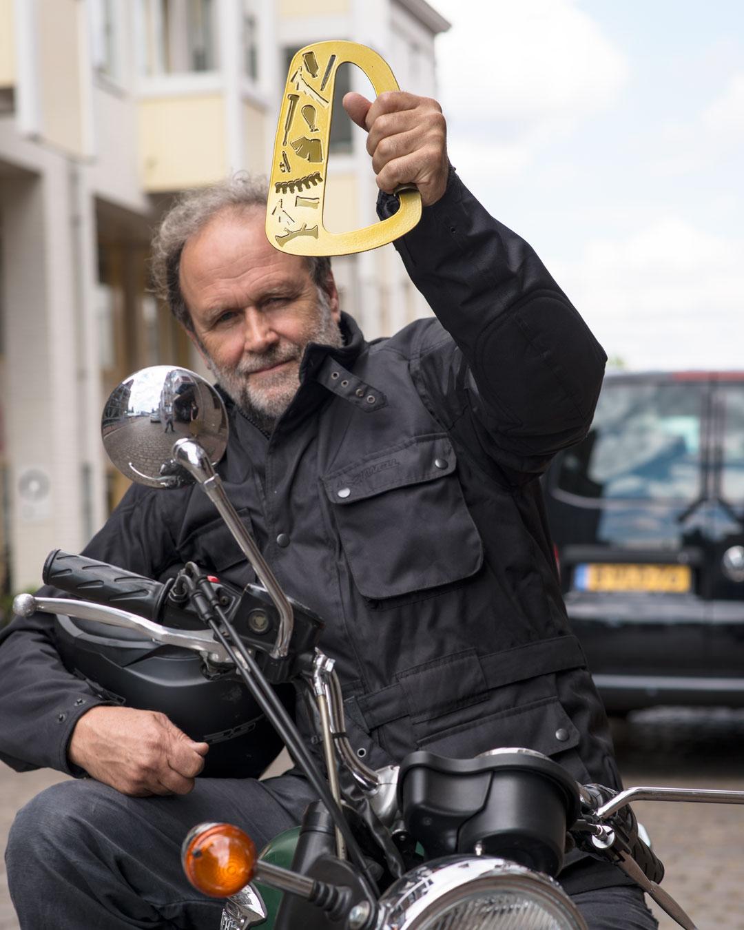 Herman Hermsen holding an object by graduate Petra Winnwalker