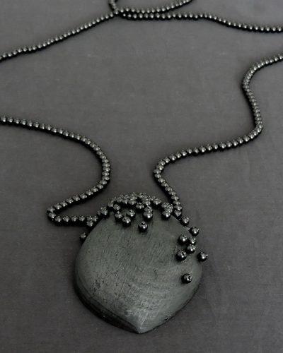 Anna Juharova, Corvus, 2020, pendant; beech charcoal, glass pearls, hematite, feathers, patinated brass, steel 87 x 58 x 20 mm