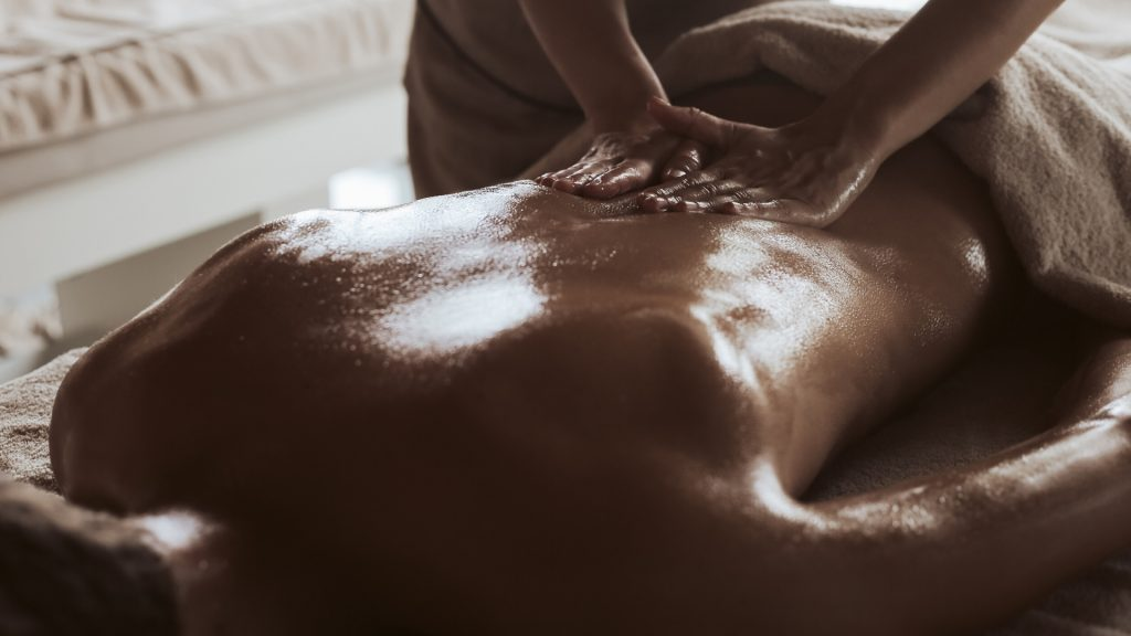 Swedish relax Massage, hands that or massaging the back of a client with a white towel over the legs