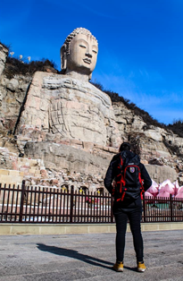 Person standing in front of a very tall Buddhist statue