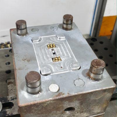 omspuiten van metalen contactpinnen voor productie van connectoren