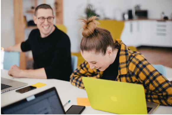 woman sat at a table laughing with a yellow laptop and a man laughing also