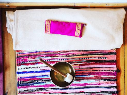 Yoga Nidra pillow on a blanket and a tibetan singing bowl