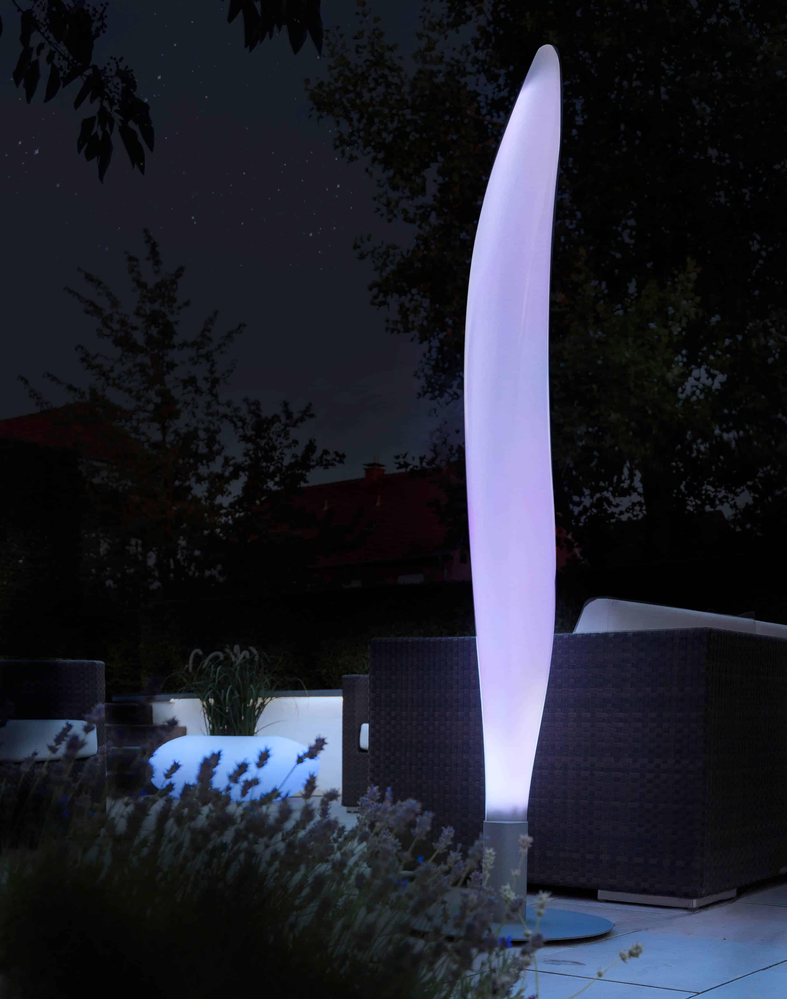 Lunocs Flame LED-verlichting met zilvergrijs voetstuk verplaatst naar buiten, op de achtergrond Storus LED