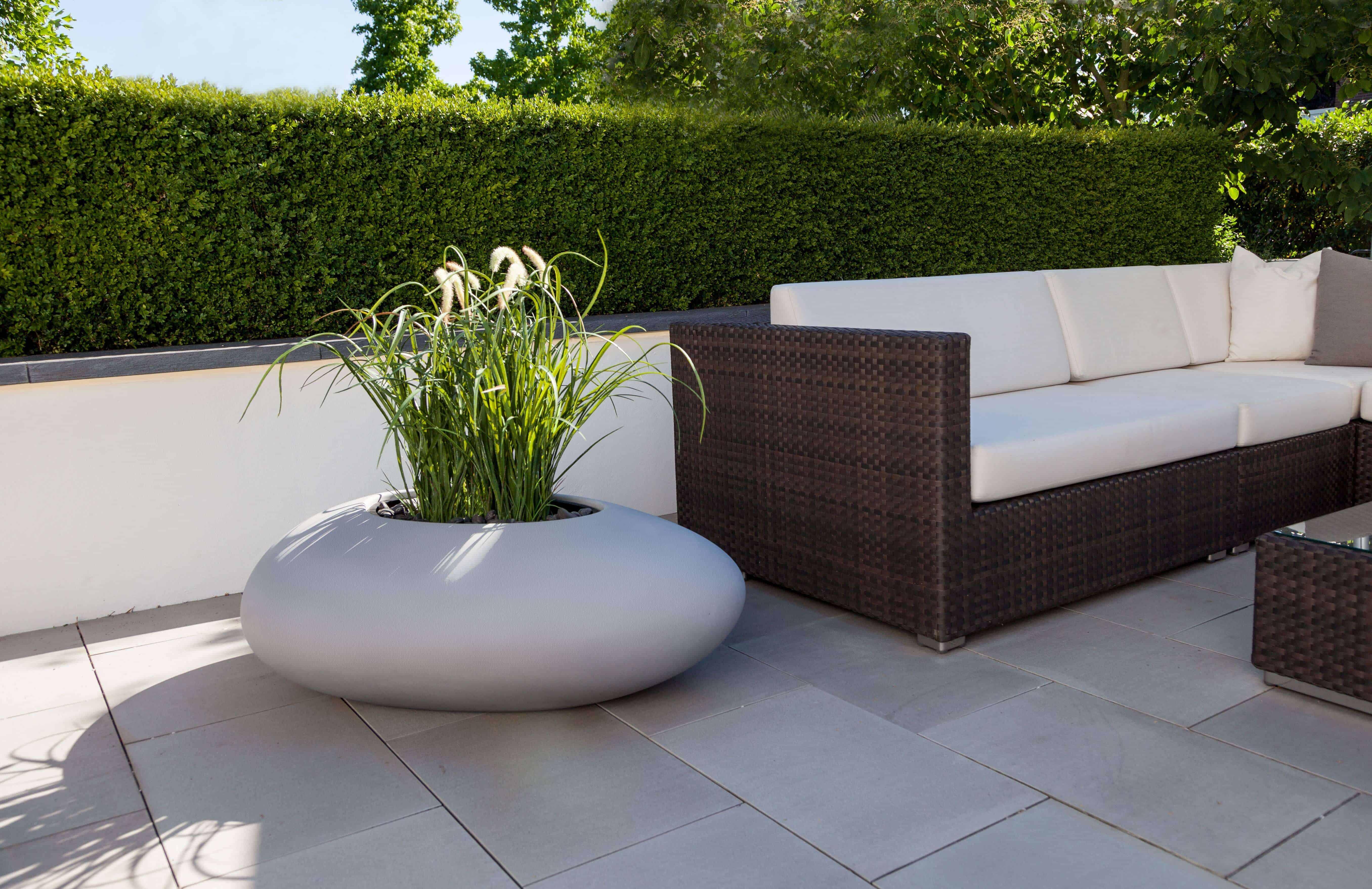 Bloembak in betonkleur in harmonie met de terrastegel