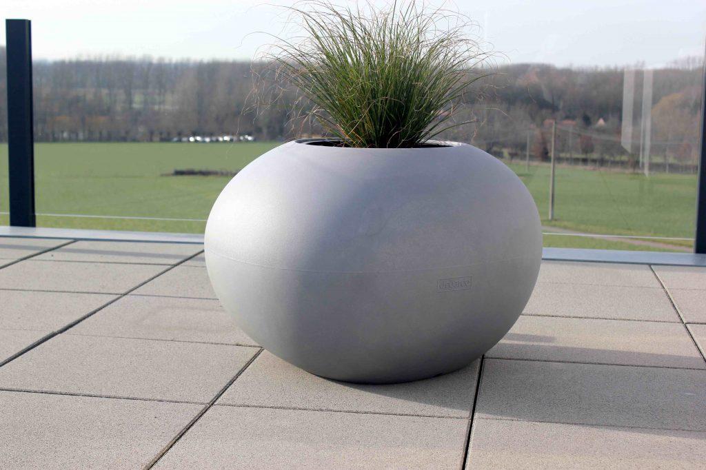 Op dakterras met betontegels kleurt deze bloembak de ruimte mooi in