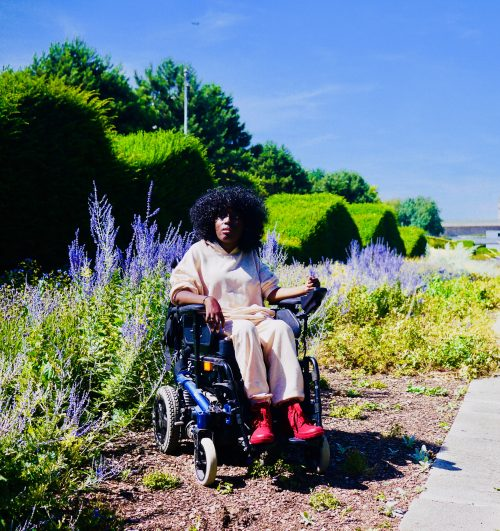 Image description: Miss Jacqui, a young black woman with loose afro hair, wearing a nude tracksuit and red boots sits in her powered wheelchair against a backdrop of fresh lavender plants, greenery and hedges trimmed in a wave. She is looking up at the sky which is blue and sunny with both arms resting on her armrests.