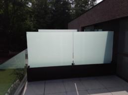 Plantenbakken met glas ter afscheiding van 2 appartementen