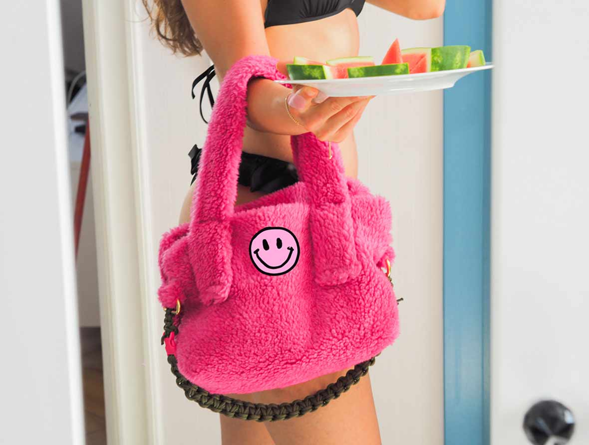 molto holding the furry teddy bag in hot pink