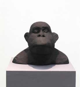 Foto på skulpturbyst av en apa i svartpatinerad gips på en sockel