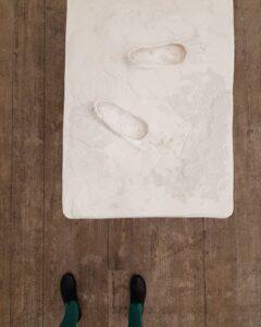 bilden visar en del av en skulptur och konstnärens fötter under utställningen It is på galleri Studio 44. A part of an sculpture in an exhibition at Studio 44 and also the artists feet.