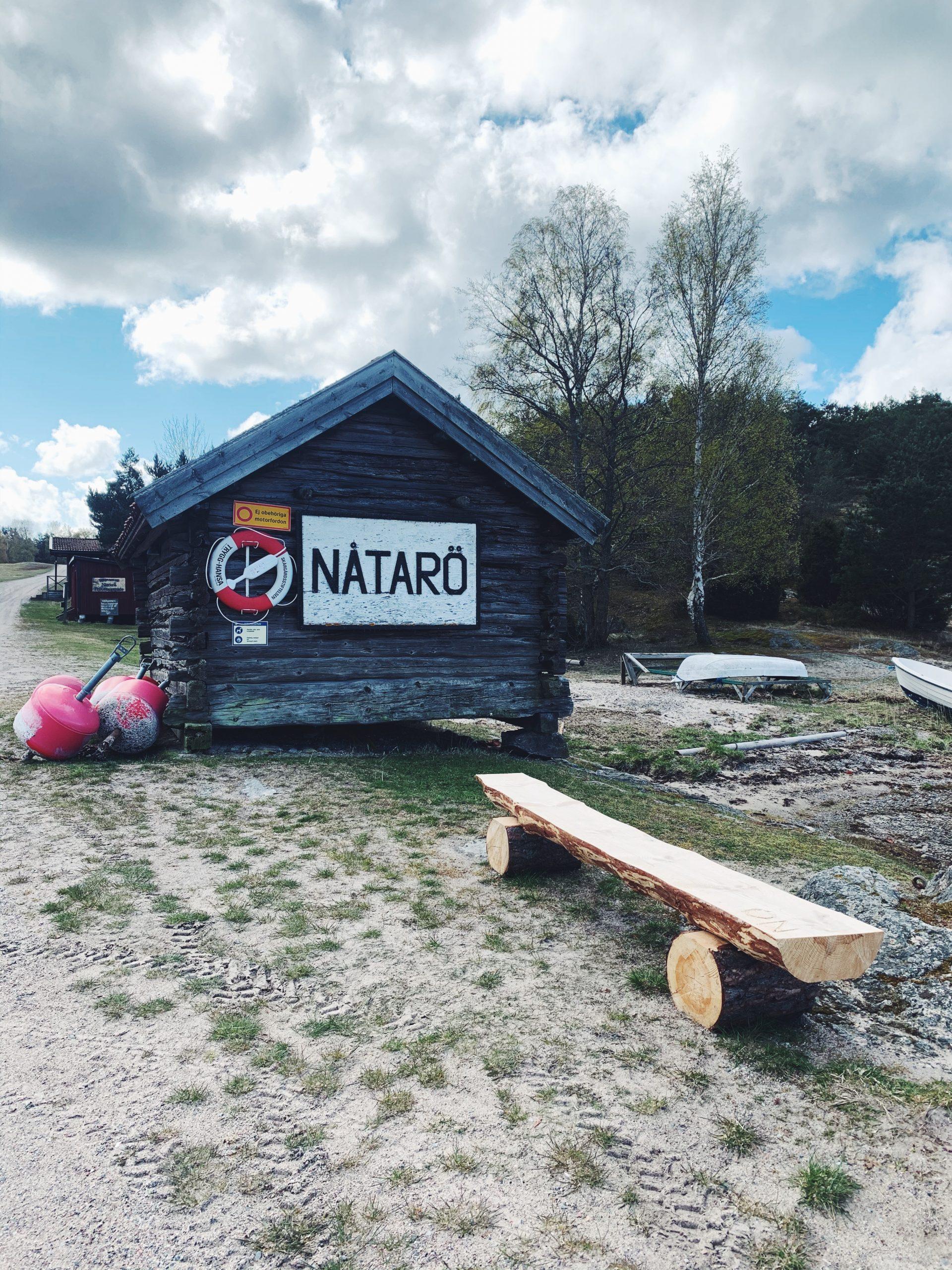 """Bild på det första en går förbi vid ankomst till Ångbåtsbryggan på Nåttarö. En gammal stuga med livboj och skylt som lyder """"Nåtarö"""", den tidigare stavningen av vår populära skärgårdsö."""