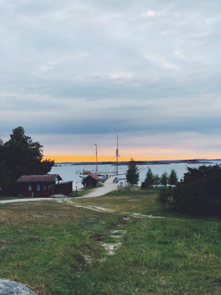 Ångbåtsbryggan från land. Ett vackert segelfartyg har lagt till vid bryggan med en bakgrund av ett apelsinfärgat sken i skyn.