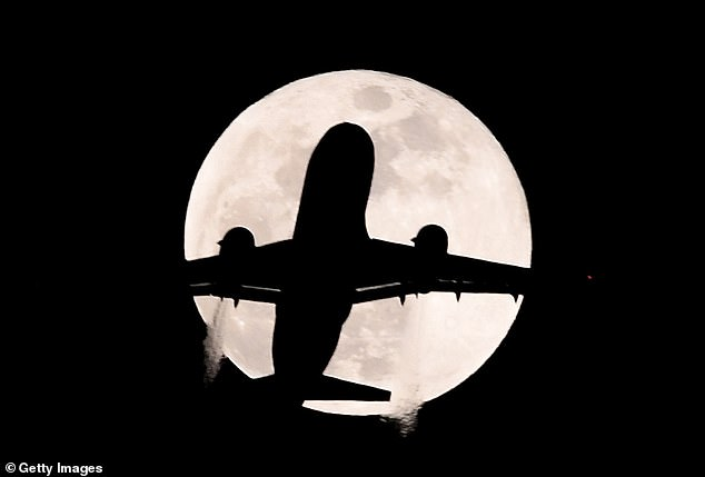 Spectators can expect the Moon to begin to darken slowly before turning red as it becomes completely caught in Earth's shade. Pictured: An aeroplane flies past a Super Moon during the Premier League match between Chelsea and AFC Bournemouth on the January 31, 2018 (file photo)