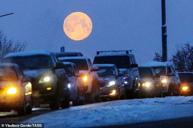 At the same time, the moon will be slightly closer to Earth and appear brighter than usual - a supermoon. Pictured: The full moon hanging over cars stuck in a traffic jam on the 1st of February in Moscow last year (file photo)