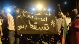 """A banner reading """"We came to protest on the street - and now it is your turn. #JustFall."""" at a sit-in at the military HQ in Khartoum, Sudan - Monday 8 April 2019"""